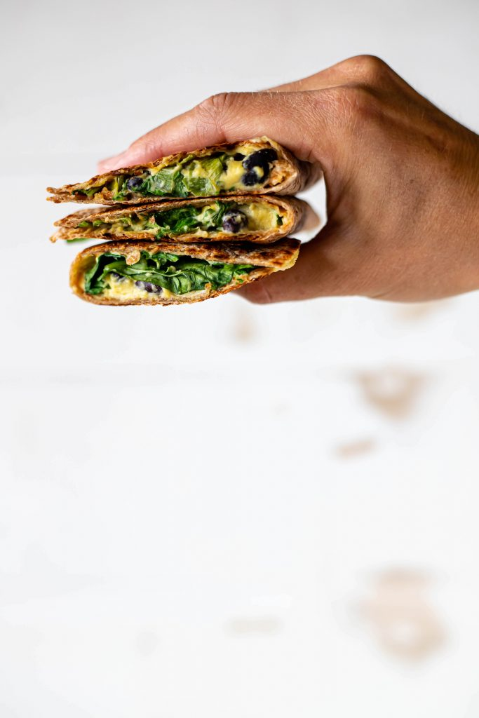 homemade cashew cheese quesadillas held in a hand