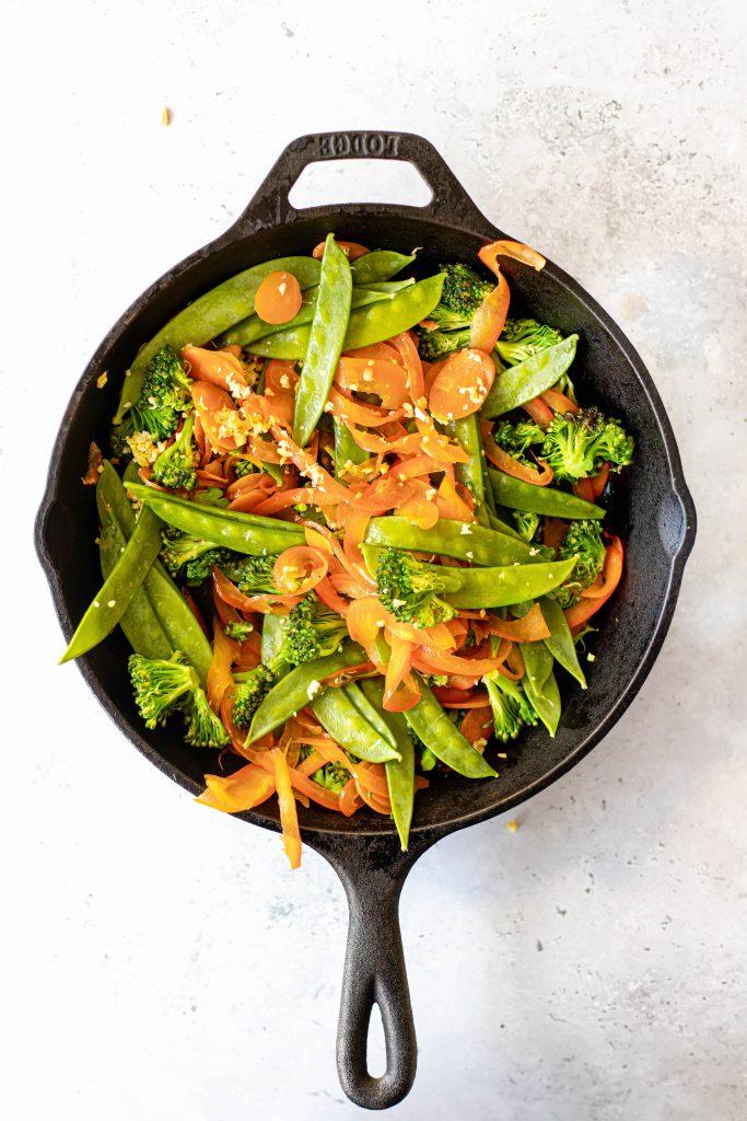 carrots, snow peas, broccoli in a cast iron